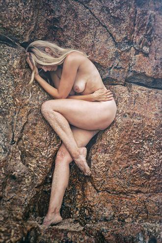 between a rock artistic nude photo by model selkie