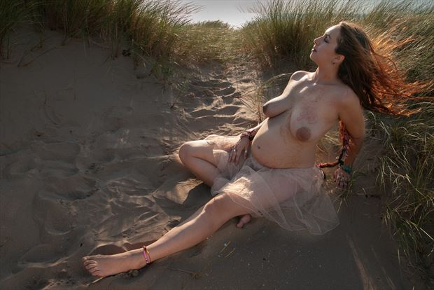 omani pregnant in the sand dunes wind blowing her hair artistic nude photo print by photographer ian cartwright